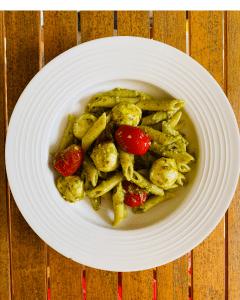 A white bowl of green pesto penne with mozzarella balls and grape tomatoes