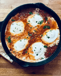 Cast iron skillet of poached eggs in tomato sauce