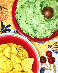 A bowl of guacamole with its pit in the center and a bowl of Fritos