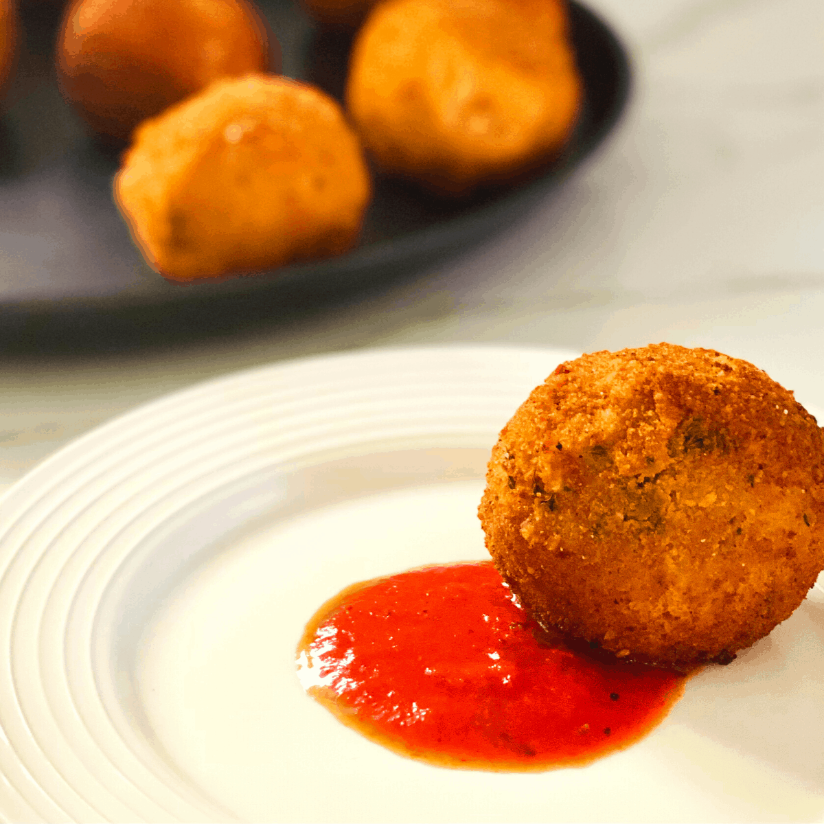 A white plate with a circle of red, marinara sauce in the center, and one fried arancini ball. A black baking pan of arancini in the background.