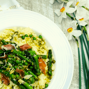 A white bowl of Spring Risotto Pesto in the bottom left corner of the photograph with white daisies with orange centers and outer red rim lay beside the right of the plate.